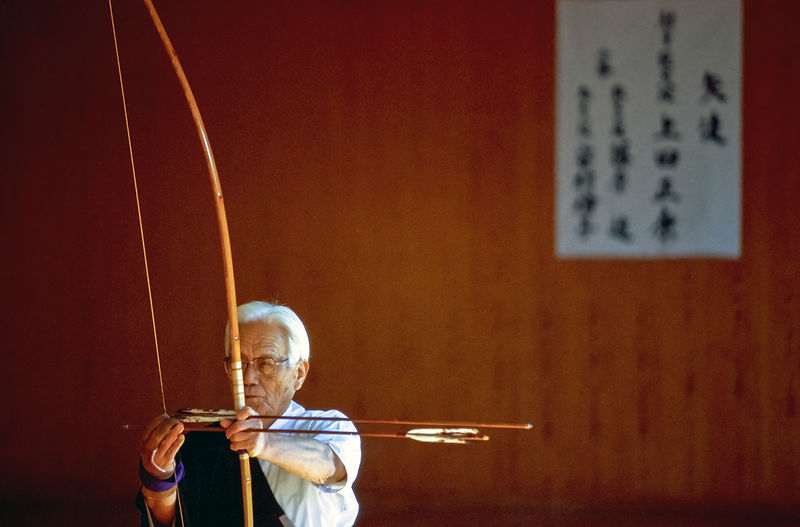 Sensei Oueda draws his bow towards the target during the opening ceremony of an archery competition, Kyoto