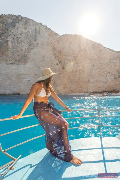 Woman on sailboat in front of famous shipwreck beach. Zakynthos, Greece