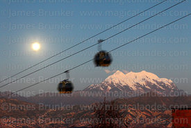 Yellow Line cable car gondolas and full moon rising above Mt Illimani, La Paz, Bolivia