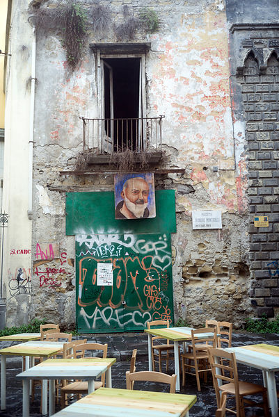 An image of Padre Pio hung from a balcony of a derelict building, Naples, Italy