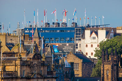 Welcome to Edinburgh Castle hoarding twoering over rooftops in Edinburgh
