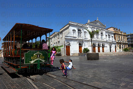Children playing with tram carriage , Municipal Theatre in background , Plaza Prat , Iquique , Chile