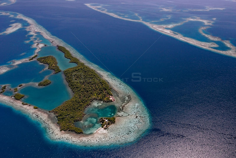 Aerial view of channel through southern Belize barrier reef, with house on small caye. Near Placencia, Belize Barrier Reef Re...
