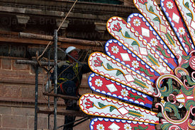 Worker putting up decorations for Corpus Christi festival in front of Compañia de Jesus church , Cusco , Peru