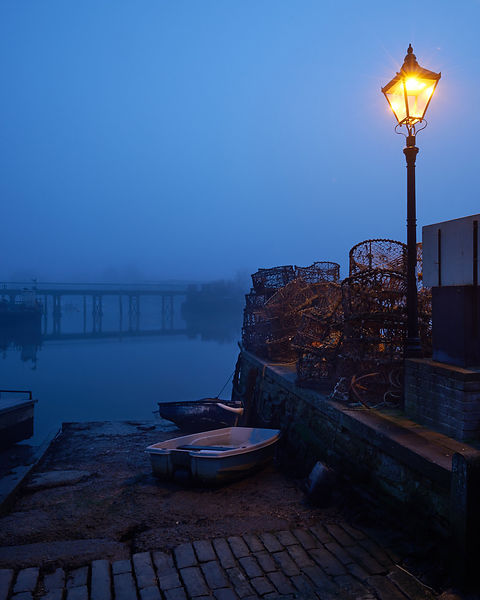 Foggy early morning on The Quay in Lymington with empty river moorings.
