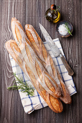 Three fresh French Baguette, extra virgin Olive oil and rosemary on gray wooden background