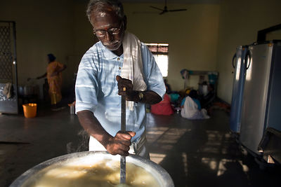India - Cuddalore - Vadivelu, 75, stirs the rice in the kitchen