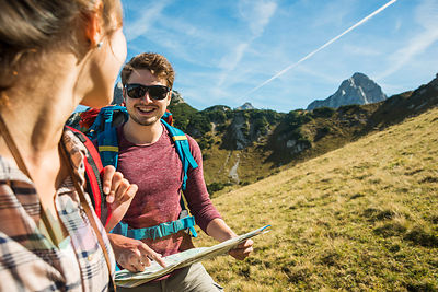 Austria, Tyrol, Tannheimer Tal, young couple hiking with map