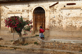 Local Quechua woman in traditional dress walking past old colonial house, Tarata, Cochabamba Department, Bolivia