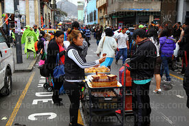 Woman selling crema volteada and other caramel desserts on street stall, Lima, Peru