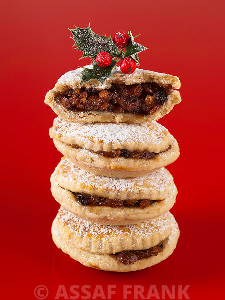 Stacked mince pies on red background with holly