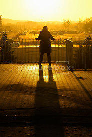 An atmospheric image of the silhouette of a mystery woman, standing and looking over a railing towards a city car park.