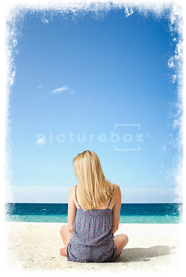 An atmospheric image of a blonde woman sitting on a tropical beach.