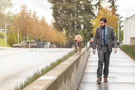 man in suit walking dog