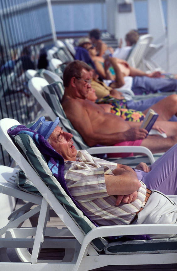 Passengers sunbathe and sleep on the deck of the P&O liner Oriana