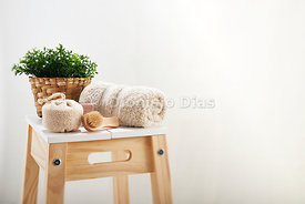 Bath utensils, towel and brushes on wooden stool