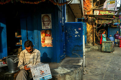 A Man Reads His Morning Newspaper Below An Image Of Sai Baba