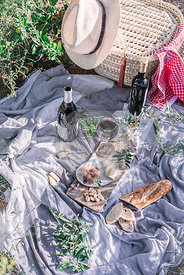 A picnic with fresh bread, cured eats and wine in the countryside
