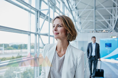Confident businesswoman at the airport looking out of window
