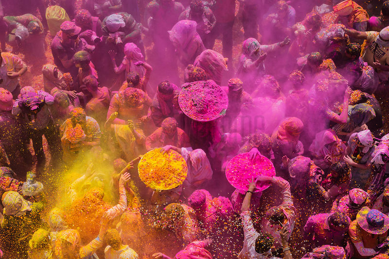Widows celebrate and dance while flowers are showered during the celebration of Holi inside Gopinath Temple