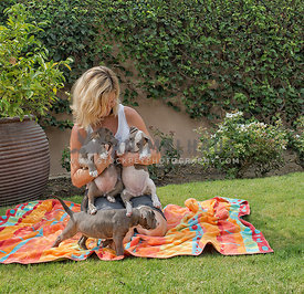 woman holding three puppies