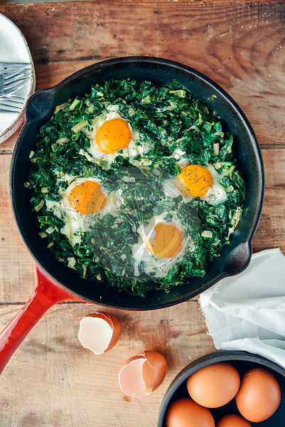 Spinach with eggs served in an iron pan photographed from top view. Eggs in a separate bowl and egg shells accompany.