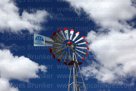 Small windmill for pumping water with Agua Sustentable / Sustainable Water written on vane, Bolivia
