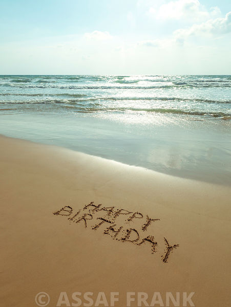 Happy Birthday written in sand on the beach
