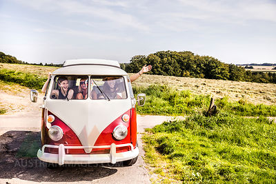 Happy friends inside van in rural landscape