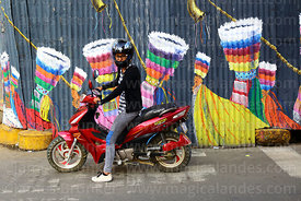 Girl on moped in front of mural with chunchus dancers painted on corrugated iron fence, Tarija, Bolivia