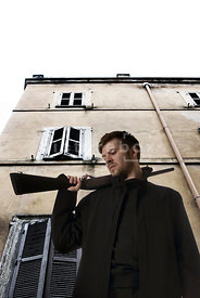 An atmospheric image looking up at a man with a pump action shotgun, in front of an old building.