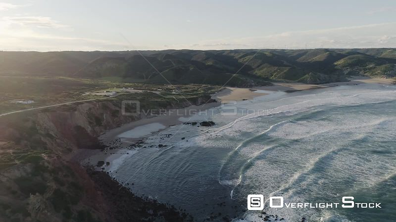 Aerial drone flying over a beautiful beach with rocky cliffs off the coast of Portugal