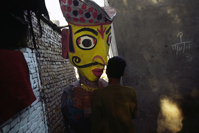 India - New Delhi - A performer carries a giant puppet through the lanes of Shadipur