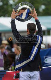 Jonathan Paget holds the Land Rover Trophy above his head - Burghley Horse Trials 2013.