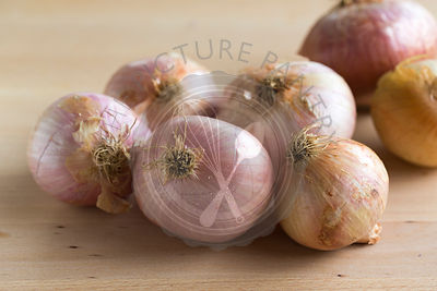 group of pink toned figuera Spanish onions on light wood table,