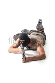 A hooded mercenary laying on the floor, pointing a rifle – shot from mid level.