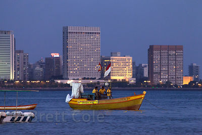 Boaters on Back Bay in the Araban Sea at night, with the Mumbai skyline in the background. Mumbai, India.