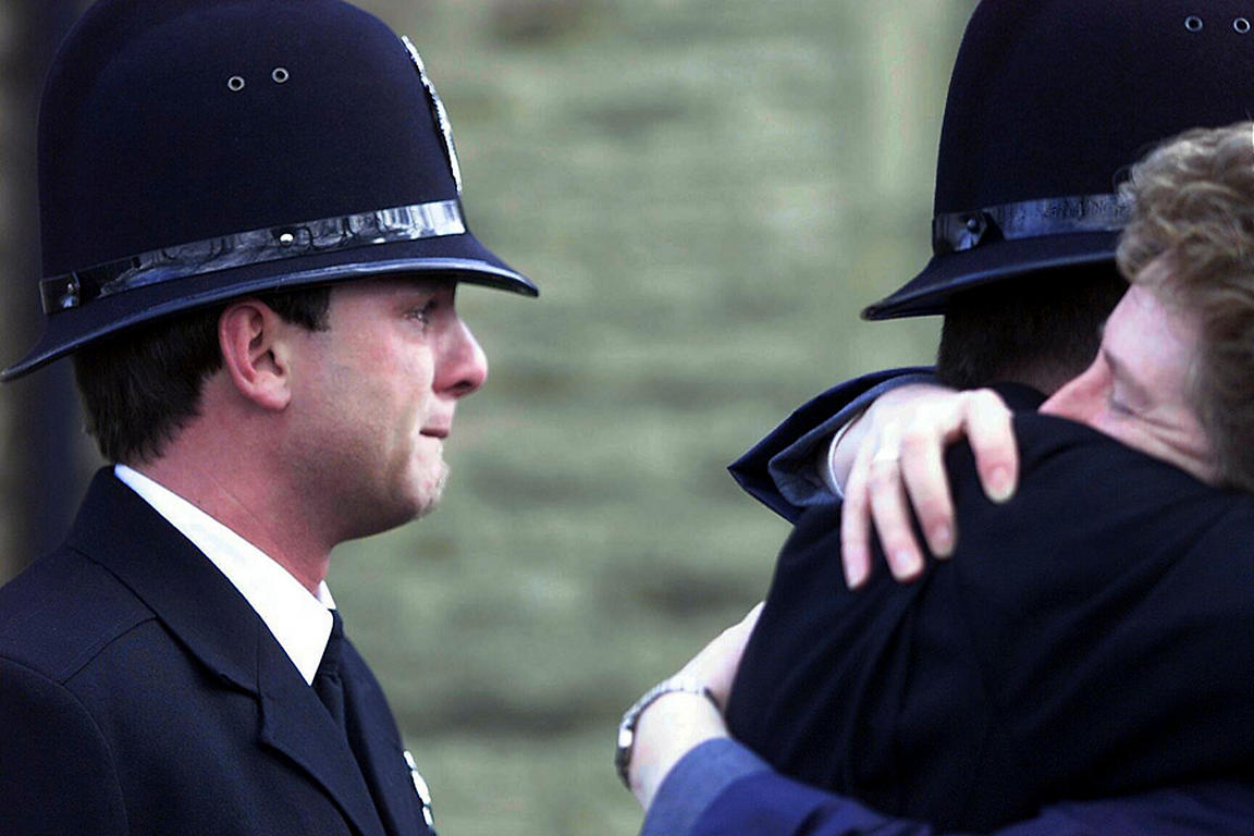 Crying policeman at a funeral