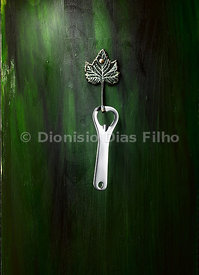 Bottle opener hanging on a hook on a green background