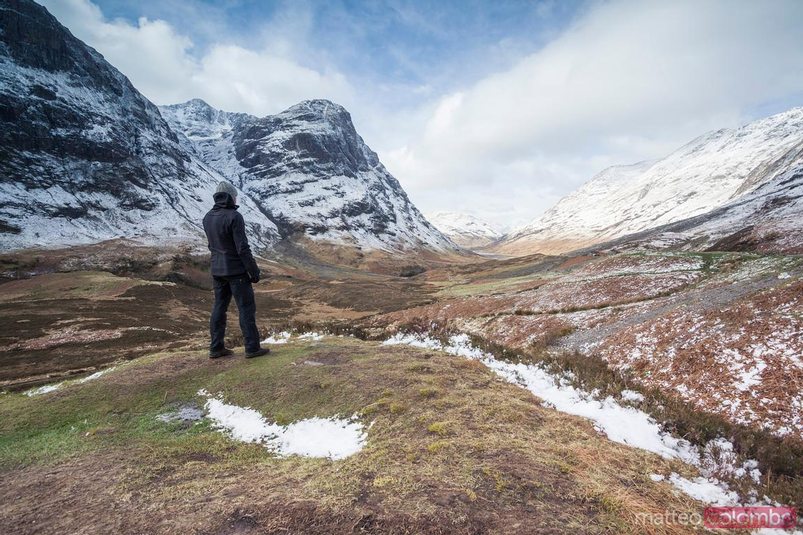 Man looking at valley and mountain range, Scotland, UK