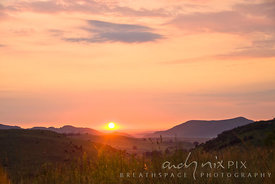 Sun rising over a hilly highveld landscape, highlighting the tips of the veld grass in the forground.