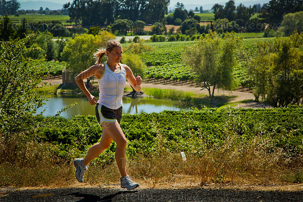 Young fit woman trail running through vineyards in Napa Valley