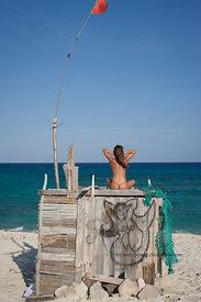 Woman sitting on top of driftwood shack with mermaid drawing on beach, east side, Cozumel, Mexico