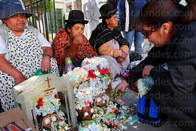 Devotee offering coca leaves to skulls in cemetery, Ñatitas festival, La Paz, Bolivia