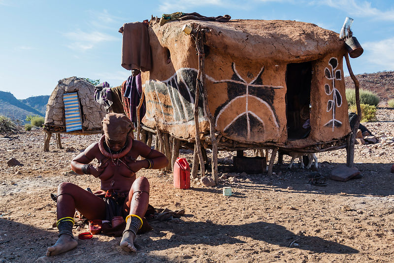 Himba Woman Applying Ochre Dye to her Skin