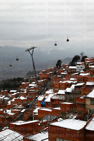 Yellow Line cable car above houses in Cotahuma district after winter snowfall, La Paz, Bolivia
