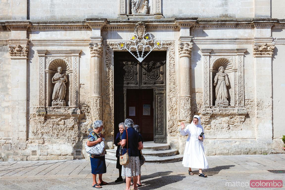 Old local women and a nun in front of church, Matera, Italy
