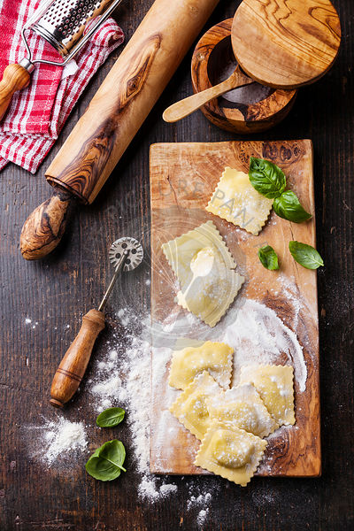 Raw Homemade Ravioli with pasta cutter on dark wooden background