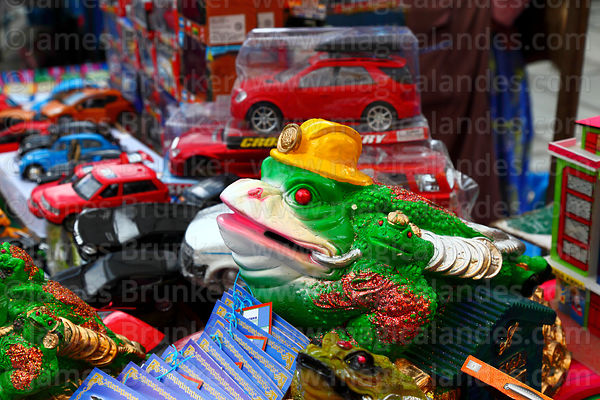Chinese Jin Chan money toad wearing miners helmet and other miniatures for sale on stall, Alasitas festival, La Paz, Bolivia