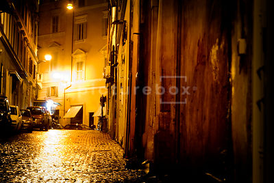 An atmospheric image of a wet, rainy,  empty, cobbled street in Rome, Italy, at night.